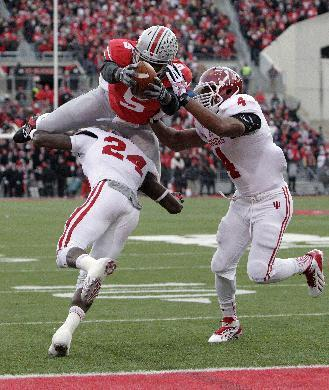 Ohio State quarterback Braxton Miller, top, scores a touchdown against Indiana's Tim Bennett, left, and Forisse Hardin during the second quarter of an NCAA college football game Saturday, Nov. 23, 2013, in Columbus, Ohio. (AP Photo/Jay LaPrete)