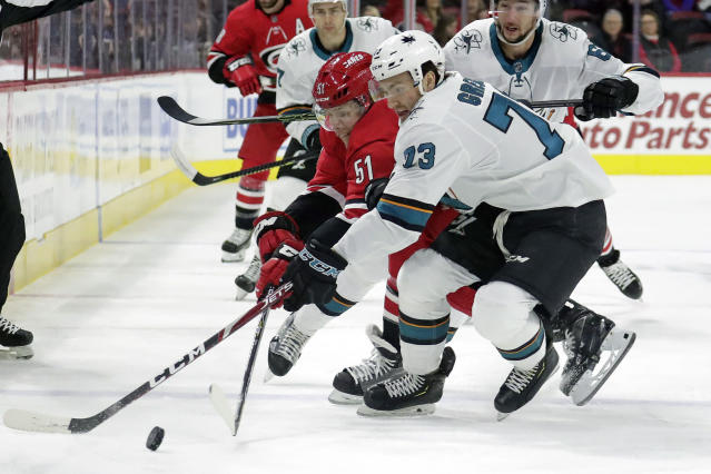 Carolina Hurricanes Jake Gardiner (51) and San Jose Sharks Noah Gregor (73) battle for the puck during the first period of an NHL hockey game in Raleigh, N.C. on Thursday, Dec. 5, 2019. (AP Photo/Chris Seward)