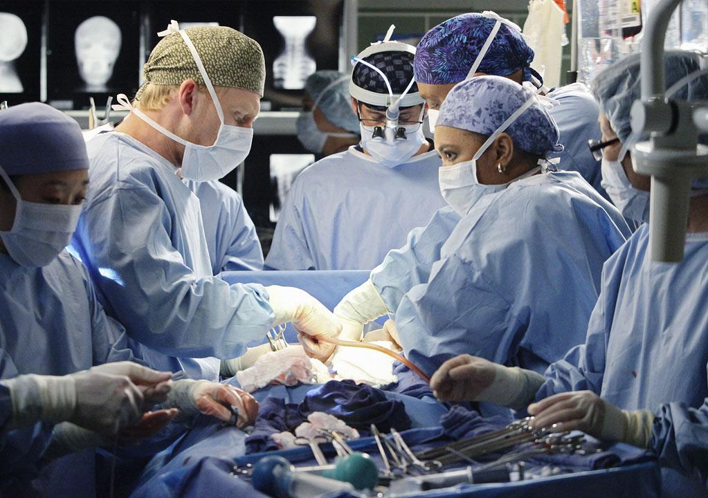 """Sandra Oh as Cristina Yang, Kevin McKidd as Owen Hunt, Patrick Dempsey as Derek Shepherd, James Pickens, Jr. as Richard Webber, and Chandra Wilson as Miranda Bailey in the """"<a href=""""/grey-39-s-anatomy/show/36657"""">Grey's Anatomy</a>"""" musical episode, """"Song Beneath the Song."""""""