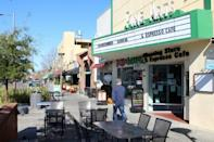 A man glances into ZombieRunner coffee shop as he strides along a quiet sidewalk in downtown Palo Alto, which is largely deserted due to people staying home over coronavirus caution