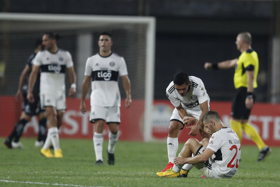 Paraguay's Olimpia players leave the pitch at the end of their Copa Libertadores soccer match against Brazil's Santos, in Asuncion, Paraguay, Thursday, Oct. 1, 2020. Brazil's Santos won the match. (AP Photo/Jorge Saenz, Pool)
