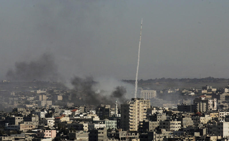 FILE - In this Tuesday, Jan. 6, 2009 file photo, a rocket fired by Palestinian militants at southern Israel leaves a thin trail of white smoke, as smoke caused by explosions from Israeli forces' operations rises from buildings on the outskirts of Gaza City. A leader of one of Gaza's secretive jihadi groups says the al-Qaida-inspired movement now has several thousand armed fighters in the seaside strip, posing a formidable threat to both Israel and the area's Hamas rulers. (AP Photos/Hatem Moussa, File)