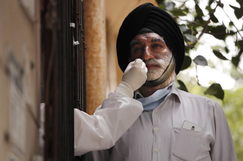 A health worker takes a nasal swab to test for COVID-19 in New Delhi, India, Saturday, Aug. 22, 2020. India has the third-highest caseload after the United States and Brazil, and the fourth-highest death toll in the world. (AP Photo/Manish Swarup)