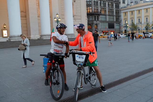 Portuguese cyclist Helder Batista, who arrived in Russia's capital to attend the 2018 FIFA World Cup, is welcomed by a man on a bike in central Moscow, Russia June 18, 2018. REUTERS/Tatyana Makeyeva