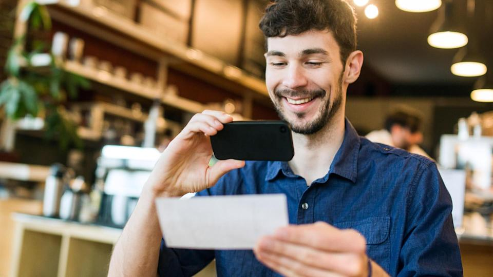 A smiling man takes a picture with his smart phone of a check or paycheck for digital electronic depositing, also known as