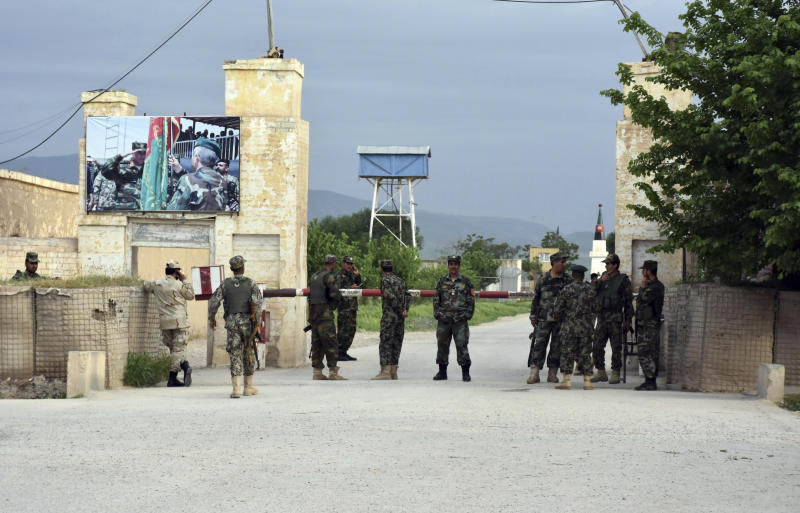 Afghan soldiers stand guard at the gate of a military compound after an attack by gunmen in Mazar-e- Sharif province north of kabul, Afghanistan, Friday, April 21, 2017. Gunmen wearing army uniforms stormed a military compound in the Balkh province, killing at least eight soldiers and wounding 11 others, an Afghan government official said Friday. (AP Photo/Mirwais Najand)
