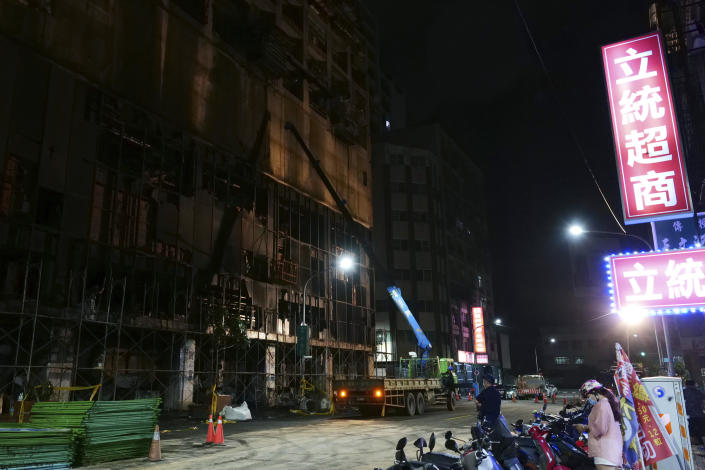 A woman stands across the street from the burnt building in Kaohsiung in southern Taiwan on Thursday, Oct. 14, 2021. Officials say at least 46 people were killed and over 40 injured after a fire broke out in a decades-old mixed commercial and residential building in the Taiwanese port city of Kaohsiunging. Neighborhood residents say the 13-story building was home to many poor, elderly and disabled people and it wasn't clear how many of the 120 units were occupied. (AP Photo/Huizhong Wu)