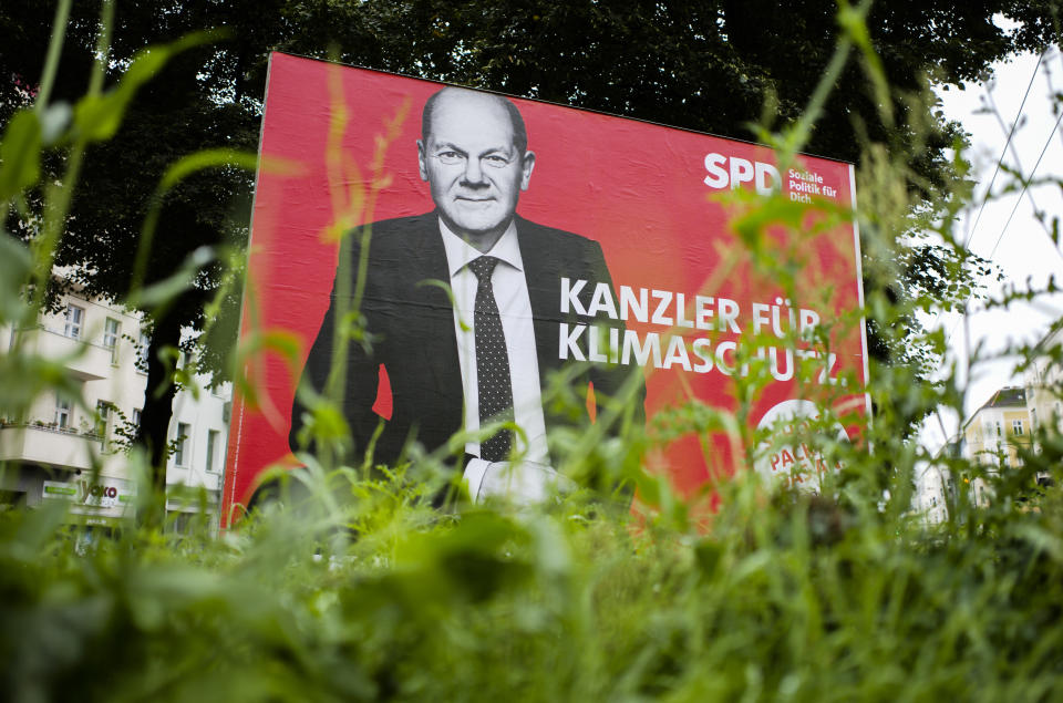 German Social Democratic Party, SPD, candidate for chancellor Olaf Scholz is displayed on an election campaign poster reading: ' Chancellor for climate protection', near a street in Berlin, Germany, Monday, Aug. 30, 2021. National election take place in Germany on Sept. 26, 2021. (AP Photo/Markus Schreiber)