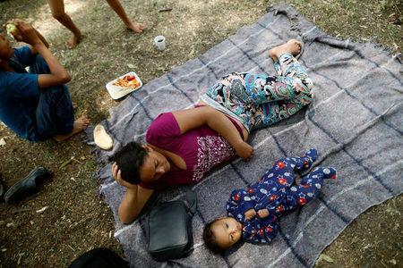Aide and her baby son Clesner from Guatemala, rest along with fellow Central American migrants, who are moving in a caravan through Mexico toward the U.S. border, at a shelter set up for them by the Catholic church, in Puebla, Mexico April 6, 2018. REUTERS/Edgard Garrido