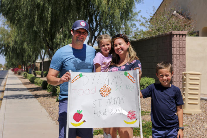 """Nick, Evelyn, Erin and Dylan Pfeifer stand together near their home in Chandler, Ariz., holding a hand-drawn sign promoting a food drive on Saturday, April 3, 2021. Dylan Pfeifer hosted his third food drive since October in response to the coronavirus pandemic. """"It's been hard to interact with people, especially now, so this provides a safe way to do that. I just wanted to provide him a way to make an impact,"""" Erin Pfeifer said. (AP Photo/Cheyanne Mumphrey)"""