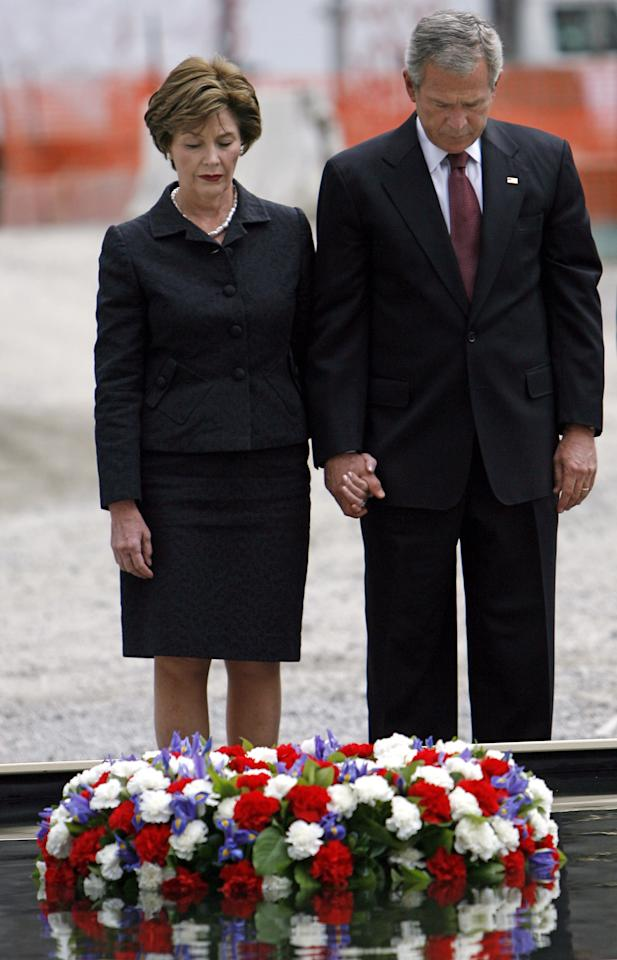 President Bush and first lady Laura Bush observe a moment of silence after laying a memorial wreath in a reflecting pool at ground zero Sunday, Sept 10, 2006. President Bush was in New York to help commemorate the fifth anniversary of the Sept. 11, 2001 terrorist attacks. (AP Photo/Jason DeCrow)
