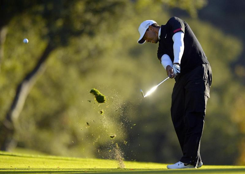 Tiger Woods makes his approach shot on the 18th hole during the third round of the Northwestern Mutual World Challenge golf tournament at Sherwood Country Club, Saturday, Dec. 7, 2013, in Thousand Oaks, Calif. (AP Photo/Mark J. Terrill)