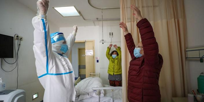 A respiratory specialist encourages a patient to exercise in a hospital in Wuhan, China, in February 2020.