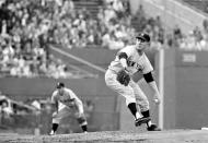 FILE - This Sept. 19, 1961, file photo shows New nYork Yankees' Whitey Ford throwing to Baltimore Orioles' Brooks Robinson during first inning action in Baltimore, Md. Sports in 2020 was an unending state of mourning. It seemed a whole wing of the Baseball Hall of Fame was ripped away -- Al Kaline, Tom Seaver, Lou Brock, Bob Gibson, Whitey Ford, Joe Morgan, Phil Niekro. (AP Photo/File)