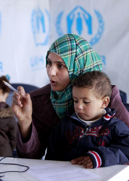 "Syrian refugee Bushra, 19, who fled her house from Homs 17 days ago, holds her son Omar, 2, as she registers at the UNHCR center in the northern city of Tripoli, Lebanon, Wednesday, March. 6, 2013. The number of Syrians who have fled their war-ravaged country and are seeking assistance has now topped the one million mark, the United Nations' refugee agency said Wednesday warning that Syria is heading towards a ""full-scale disaster."" (AP Photo/Bilal Hussein)"