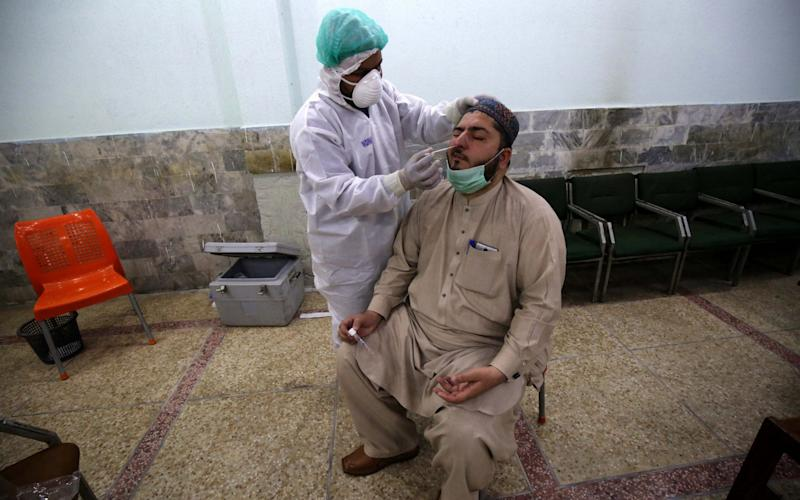 A health official conducts a COVID-19 test on a journalist in Peshawar, Pakistan 03 June 2020. Countries around the world are taking increased measures to stem the widespread of the SARS-CoV-2 coronavirus which causes the Covid-19 disease. Coronavirus COVID-19 testing in Pakistan, Peshawar - 03 Jun 2020 - Shutterstock