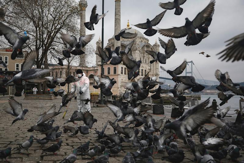 """A municipality worker wearing a protective suit is surrounded by pigeons as he cleans the Ortakoy square in Istanbul, backdropped by the Ottoman-era Mecidiye mosque and the """"July 15th Martyrs' bridge, formerly known as Bosporus Bridge, over the Bosporus Strait, separating Europe and Asia, amid the coronavirus outbreak, on March 23."""