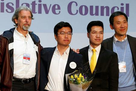 (L-R) Pro-democracy candidates Paul Zimmerman, Au Nok-hin, Gary Fan and Edward Yiu pose on the podium after the Legislative Council by-election in Hong Kong, China March 12, 2018.      REUTERS/Bobby Yip