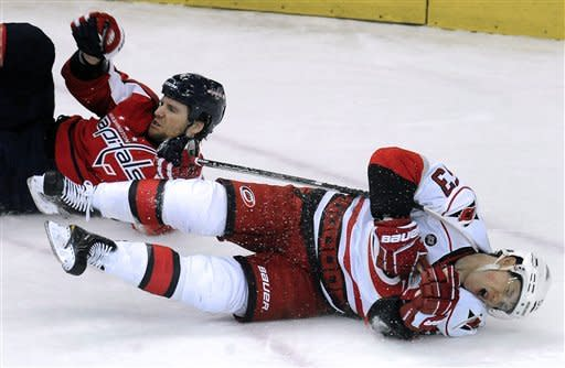 Carolina Hurricanes' Jeff Skinner (53) hits the ice after colliding with Washington Capitals' Dennis Wideman during the third period of their NHL hockey game, Sunday, Jan. 15, 2012, in Washington. The Capitals defeated the Hurricanes 2-1. (AP Photo/Richard Lipski)