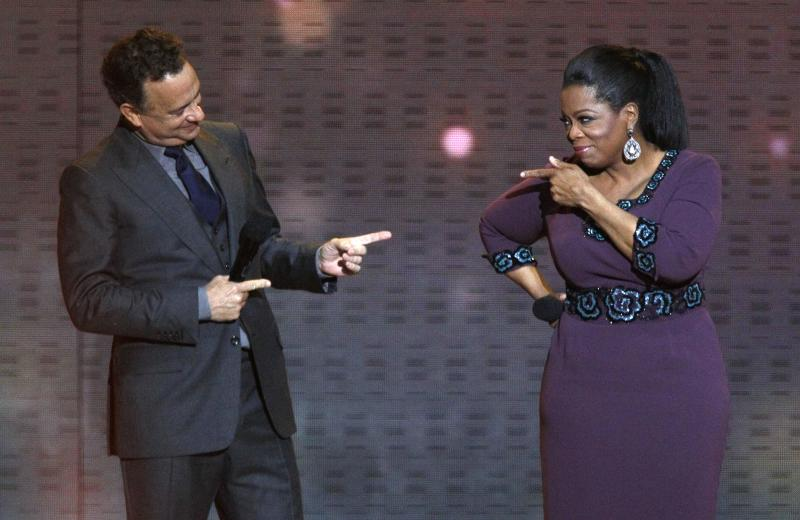 "Tom Hanks talks to Oprah Winfrey during a star-studded double-taping of ""Surprise Oprah! A Farewell Spectacular,"" Tuesday, May 17, 2011, in Chicago. ""The Oprah Winfrey Show"" is ending its run May 25, after 25 years, and millions of her fans around the globe are waiting to see how she will close out a show that spawned a media empire. (AP Photo/Charles Rex Arbogast)"