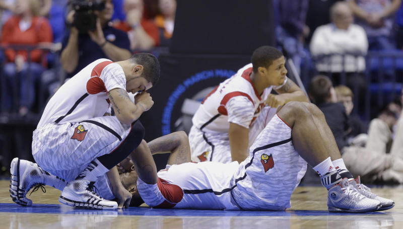 Louisville's Peyton Siva, left, Chane Behanan, center, and Wayne Blackshear (20) react to LKevin Ware's injury during the first half of the Midwest Regional final in the NCAA college basketball tournament, Sunday, March 31, 2013, in Indianapolis. (AP Photo/Michael Conroy)