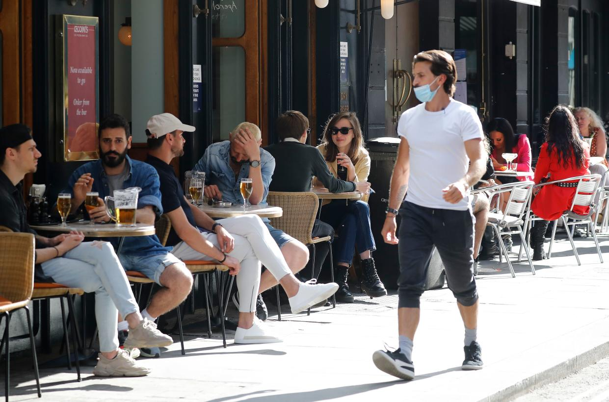 """A man wearing a face mask or covering due to the COVID-19 pandemic, walks past consumers sat outside a restaurant in London on August 3, 2020, as the Government's """"Eat out to Help out"""" coronavirus scheme to get consumers spending again gets underway. - Britain's """"Eat out to Help out"""" scheme began Monday, introduced last month by Chancellor Rishi Sunak to help boost the economy claw its way from a historic decline sparked by the coronavirus crisis. (Photo by Tolga AKMEN / AFP) (Photo by TOLGA AKMEN/AFP via Getty Images)"""
