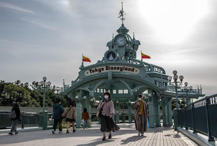 People pass beneath an archway leading to Tokyo Disneyland on the day it announced it will close until March 15 because of concerns over the COVID-19 virus. A growing number of events and sporting fixtures are being cancelled or postponed around Japan while some businesses are closing or asking their employees or work from home. Feb. 28, 2020
