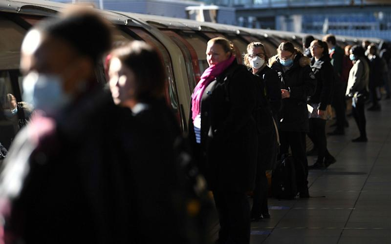 Commuters wait to board a train at Canning Town underground station - Victoria Jones/PA