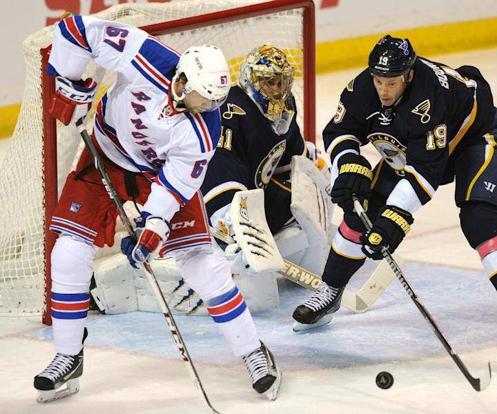 St. Louis Blues' goalie Jaroslav Halak (41), of Slovakia, and Jay Bouwmeester (19) defend against New York Rangers' Benoit Pouliot (67) during the second period of an NHL hockey game on Saturday, Oct. 12, 2013, in St. Louis. (AP Photo/Bill Boyce)