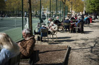 People, some wearing face masks to prevent the spread of the coronavirus, enjoy the sun in an outdoor seating area in Luxembourg gardens, in Paris, Monday, April 19, 2021.(AP Photo/Lewis Joly)