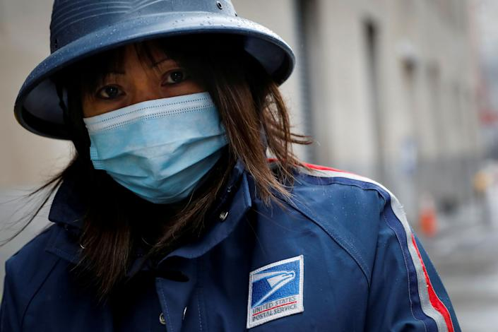 A USPS employee works in the rain in Manhattan during the outbreak of the coronavirus in New York City on April 13, 2020. (Photo: REUTERS/Andrew Kelly)