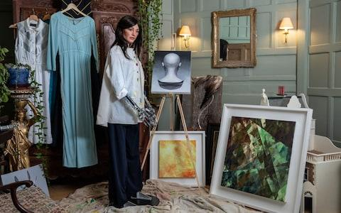At home in her studio: Ai-Da next to one of her shattered light compositions - Credit: Nicky Johnston