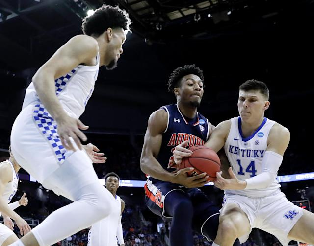 Kentucky's Tyler Herro (14) tries to grab the ball away from Auburn's Anfernee McLemore, center, as Kentucky's EJ Montgomery, left, watches during the first half of the Midwest Regional final game in the NCAA men's college basketball tournament Sunday, March 31, 2019, in Kansas City, Mo. (AP Photo/Charlie Riedel)