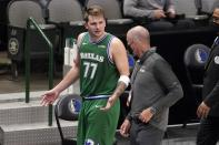 Dallas Mavericks guard Luka Doncic (77) talks with a team staff member as he walks off the court after being ejected late in the second half of an NBA basketball game against the Sacramento Kings in Dallas, Sunday, May 2, 2021. (AP Photo/Tony Gutierrez)