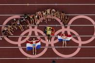 The athletes fropm the women's heptathlon pose for a picture on the Olympic rings at the 2020 Summer Olympics, Thursday, Aug. 5, 2021, in Tokyo. (AP Photo/Morry Gash)