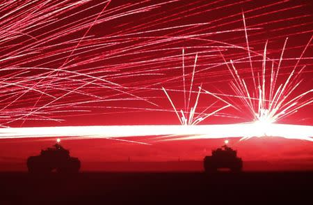 Tracer bullets ricochet off their targets as Japanese Ground Self-Defence Force tanks fire their machine guns during a night session of an annual training exercise in Gotemba