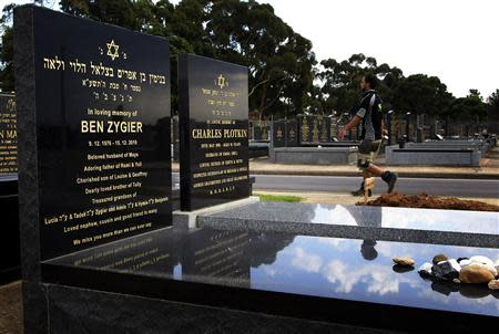 A workman walks through a Jewish cemetery, past the grave of Ben Zygier, in Melbourne