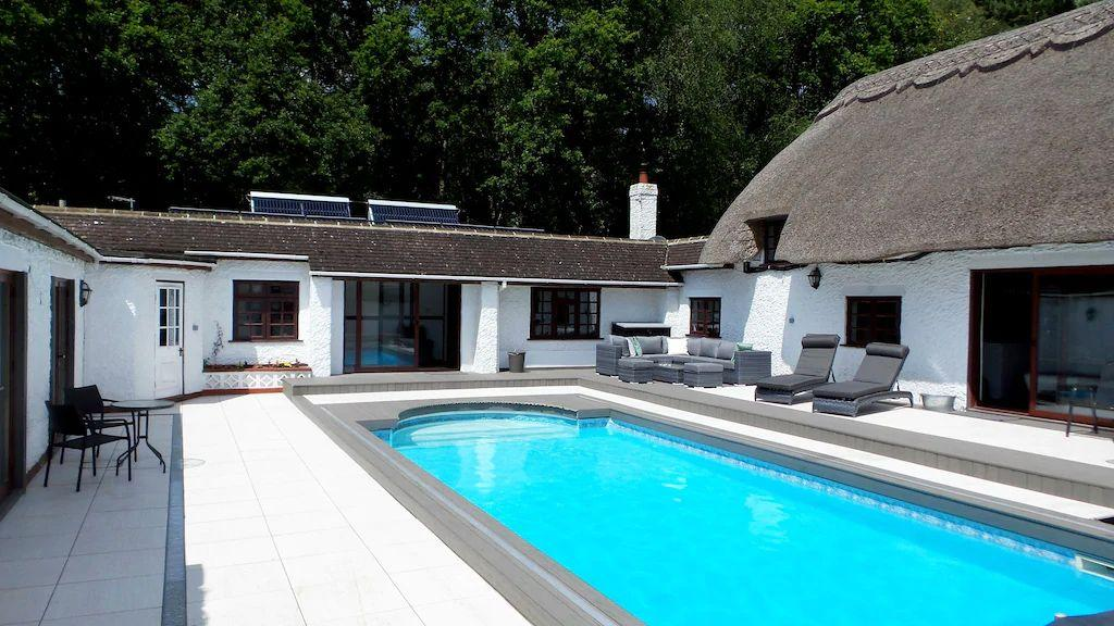 "<p>This beautiful thatched cottage with a pool on the Dorset/Hampshire border is ideal for lovers of the outdoors. It's made for big groups of 22 and you'll find plenty of spaces to relax together, from the outdoor swimming pool to the eight-person <a href=""https://www.womenshealthmag.com/uk/fitness/fitness-holidays/g28585380/best-airbnbs-with-hot-tubs/"" target=""_blank"">hot tub</a>. The beautiful barn is perfect for trying out your favourite healthy recipes on the gang and there are outdoor outdoor games like football, croquet and badminton to enjoy getting active in a fun style.</p><p><strong>Sleeps:</strong> 22</p><p><strong>Pets: </strong>Yes</p><p><strong>Bring:</strong> A <a href=""https://www.womenshealthmag.com/uk/fitness/strength-training/a26959575/health-headlines-thirty-three/"" target=""_blank"">meditation</a> cushion. The outdoor space is stunning and there's even a fish pond with Koi.</p><p><strong>Price: </strong>3 nights from £2,958</p><p><strong>Available from: </strong><a href=""https://go.redirectingat.com?id=127X1599956&url=https%3A%2F%2Fwww.homeaway.co.uk%2Fp8310223&sref=https%3A%2F%2Fwww.womenshealthmag.com%2Fuk%2Ffitness%2Ffitness-holidays%2Fg33559308%2Fcottages-with-pools%2F"" target=""_blank"">HomeAway</a></p>"
