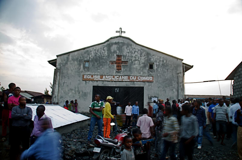 Bystanders gather around an Anglican church that was struck by mortars, wounding at least three, according to one witness, in Goma, eastern Congo, Thursday, Aug. 22, 2013. Neighbors said at least five civilians were hit by mortar fire in Goma on Thursday during a second day of heavy fighting between government forces and M23 rebels to the north of the town. The violence marked the first reports of civilians being wounded inside the city since late May, and prompted the United Nations peacekeeping mission to issue a statement saying it would take the 'necessary steps to protect civilians.'(AP Photo/Joseph Kay)