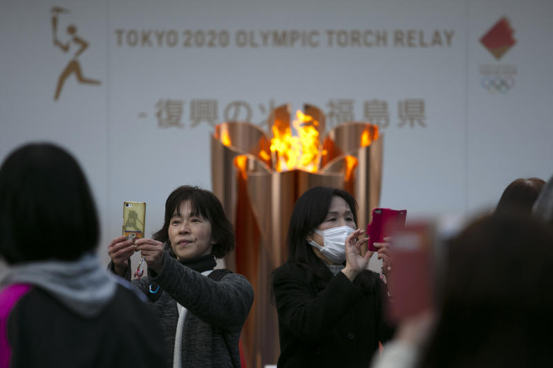 People take pictures with the Olympic Flame during a ceremony in Fukushima City, Japan, Tuesday, March 24, 2020. The Tokyo Olympic torch relay will start Thursday as planned in northeastern Fukushima prefecture, but with no torch, no torchbearers, no public, and little ceremony. (AP Photo/Jae C. Hong)