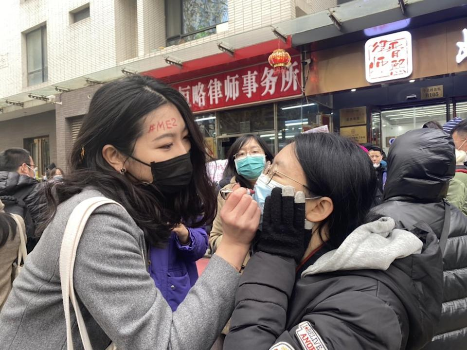 A supporter of Zhou Xiaoxuan uses lipstick to write #MeToo on a fellow supporter's mask in Beijing.