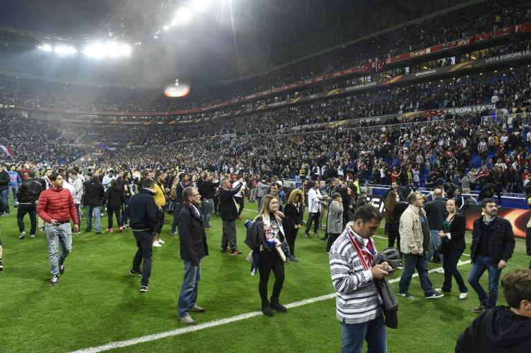 People stand on the pitch as Besiktas and Lyon fans fight before their UEFA Europa League first leg quarter final match on April 13, 2017, at the Parc Olympique Lyonnais stadium in Decines-Charpieu, central-eastern France