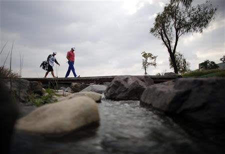 Luke Guthrie of U.S. walks to the ninth hole during the BMW Masters 2013 golf tournament at Lake Malaren Golf Club in Shanghai October 25, 2013. REUTERS/Carlos Barria