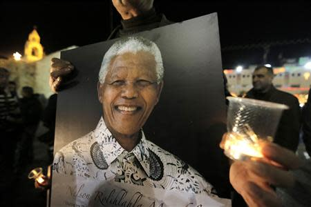 Palestinians light candles and hold placards bearing images of former South African President Nelson Mandela outside the Church of Nativity in the West Bank town of Bethlehem December 7, 2013. REUTERS/Ammar Awad