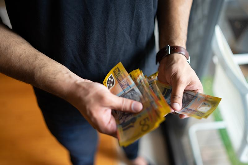 Pictured: Man holding wads of Australian cash. Image: Getty