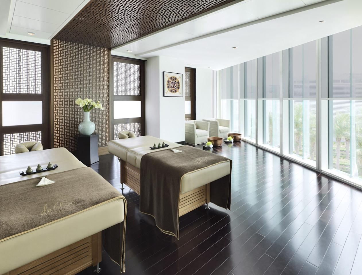 """<p><strong>What's the vibe at this place?</strong> Classy and indulgent, much like its <a href=""""https://www.cntraveler.com/hotels/abu-dhabi/four-seasons-hotel-abu-dhabi-at-al-maryah?mbid=synd_yahoo_rss"""">Four Seasons</a> home, the stylish Dahlia Spa, a 21,500-foot space, has the only quartz sand therapy treatment in the emirate. The third-floor wellness space exudes intimacy, extravagance, and relaxation.</p> <p><strong>Take us into the room. How was the session itself?</strong> Treatment rooms are spacious and welcoming, with crisp whites, chocolate browns, and statement mashrabiya (locally inspired wooden latticework). Our facialist was friendly and thorough; the scents were understated yet fresh; the music was soothing and products hailed from high-end brands like Swiss Perfection, MarocMaroc, Sodashi, and Biologique Recherche.</p> <p><strong>What about after the treatment?</strong> After our 60-minute anti-aging facial, we headed upstairs to the light-filled relaxation area. Robes and fluffy brown towels were plush and comfortable.</p> <p><strong>What do they do best here, then? And how can we make sure we get the most out of it?</strong> Our skin was brighter at the end of the hour—an impressive feat. Be sure to visit at least 30 minutes ahead of time to enjoy the dedicated men's and women's wet areas, where you can soak in the hydrotherapy pool, use the steam room, or relax on one of the heated loungers.</p>"""