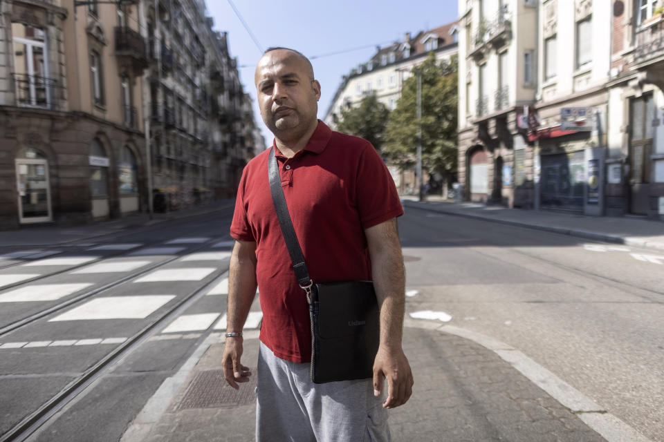 """Afghanistan's Abdul Wali poses in the middle of a street in Strasbourg, eastern France, Sunday, Sept. 4, 2021. Wali took the last bus out of a huge makeshift migrant camp in the northern French port of Calais. His government bus took him to Strasbourg. """"Now, I'm so happy to be here,"""" he said. """"You're not scared at night"""" like in the migrant camp nicknamed The Jungle. """"You have your job. You have your work, you come back home. You pay your rent. You are a normal person."""" (AP Photo/Jean-Francois Badias)"""
