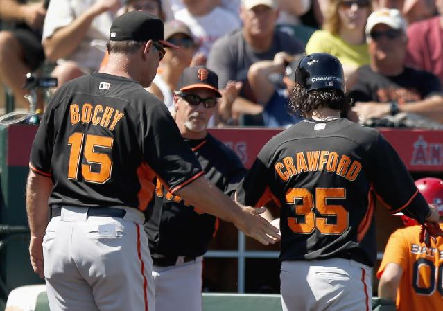 San Francisco Giants' Brandon Crawford (35) is congratulated by manager Bruce Bochy (15) and bench coach Ron Wotus after Crawford scores a run against the Los Angeles Angels during the third inning of a spring training baseball game Monday, March 24, 2014, in Tempe, Ariz. (AP Photo/Ross D. Franklin)