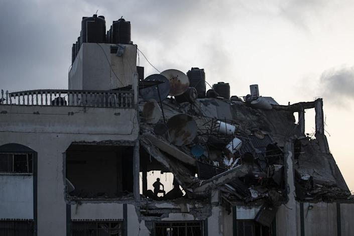 A silhouette of a person on the upper level of a damaged building