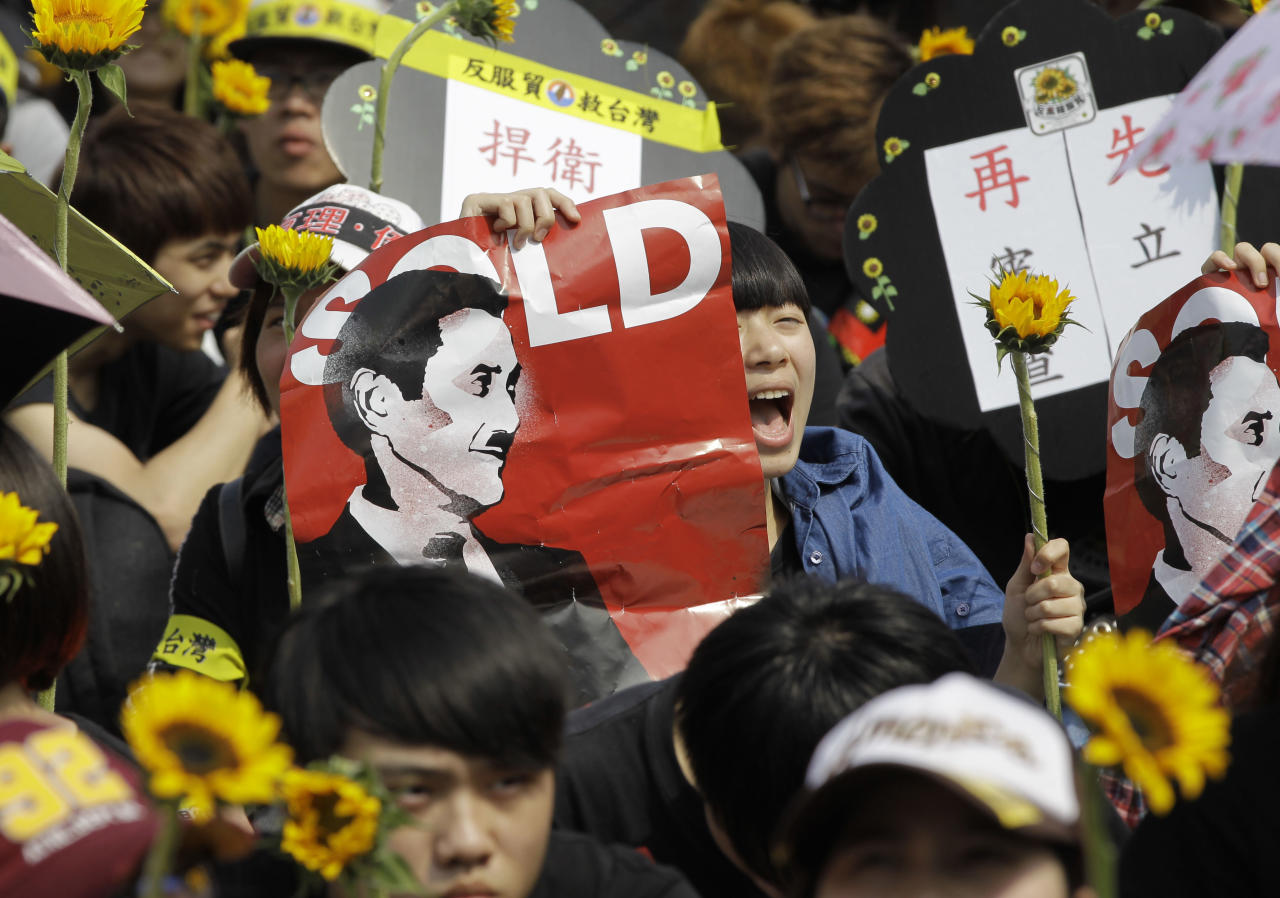 A protester holds a banner depicting Taiwanese President Ma Ying-jeou as Hitler while shouting slogans denouncing the controversial China Taiwan trade pact during a massive protest in front of the Presidential Building in Taipei, Taiwan, Sunday, March 30, 2014. Over a hundred thousand protesters gathered in the demonstration against the island's rapidly developing ties with the communist mainland. (AP Photo/Wally Santana)